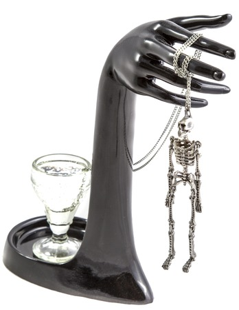 sobriety: The composition of a glass on a stand in the form of arms and hung on the fingers of a skeleton on a white background. Stock Photo