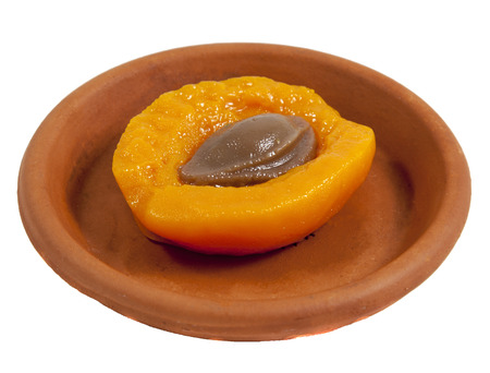 apricot kernel: Still half of apricot with a stone on brown ceramic plate on a white background