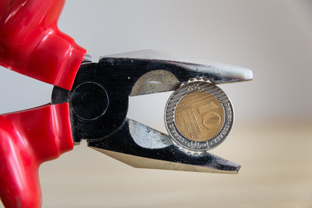 Tight budget concept shown using pliers Stock Photo