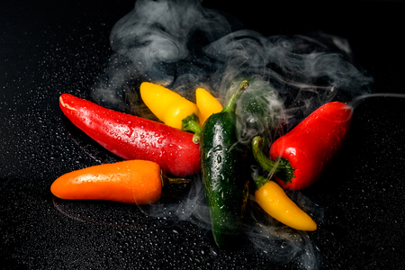 spicy red chilli shrouded in smoke Stock Photo