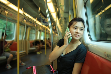 traveller: pick up the phone call go to the destination, talk on smart phone with good news, beautiful lady watch outside, in railroad box car MTR, hong kong,china, asia