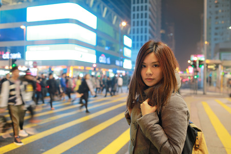 shopping scenes: Beautiful young girl stand out and watching at night in hong kong, lost in city , busy crowd and yellow zebra crossing blurred background  Stock Photo