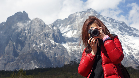 love pic: Young girl photographer holding a camera, she force on other, with snow mountain Jade Dragon background in Lijiang,  in winter, in Yunnan China wide mountain range