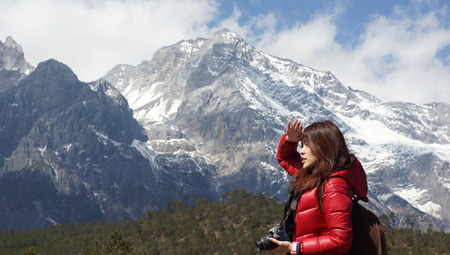love pic: Chinese asian girl model under the snow mountain ridge background, fall into a trance, taking picture, taking photo in Lijiang, Yunnan province