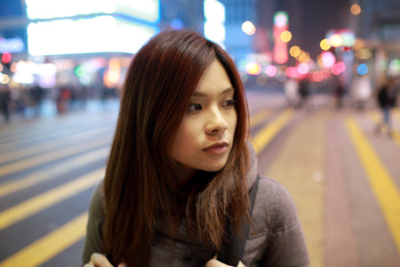 shopping scene: Beautiful young girl stand out and watching at night in hong kong, lost in city , busy crowd and yellow zebra crossing blurred background  Stock Photo