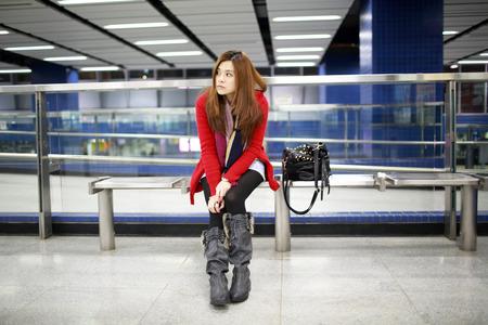 girl waiting someone so long in the modern train platform in hong kong photo