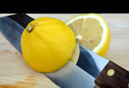 cut off: cut off yellow lemon by knife in the kitchen for cooking