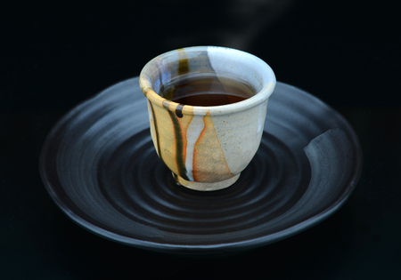 original plate: hot japanese tea serve on tea break only in  handmade cup and original plate style Stock Photo