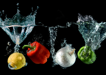 splash mixed: Splash water with droping bell pepper ,lemon and onion in art mixed in studio technical speed and lighting. Stock Photo