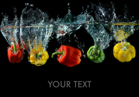 splash mixed: Splash water with droping bell peppers in art mixed whith space of text in studio technical speed and lighting.