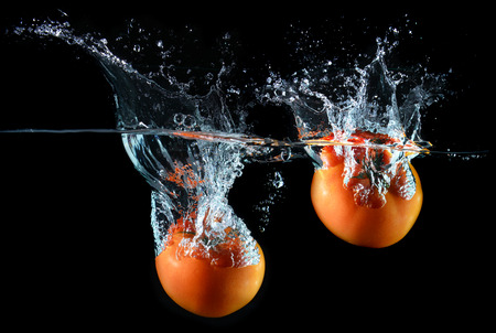 splash mixed: Splash of water droping tomatoes and art mixed in studio technical speed and lighting.
