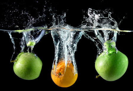 splash mixed: Splash water with droping oranges and apples in art mixed in studio technical speed and lighting. Stock Photo