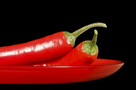 Chile pepper pods on a red glass dish