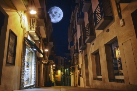 old moon: The moon illuminates the sleeping town. Spain, Costa Brava, Palamos.