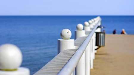 Sea pier railing with a painted smiley