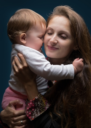 Young beautiful woman hugging her little daughter photo