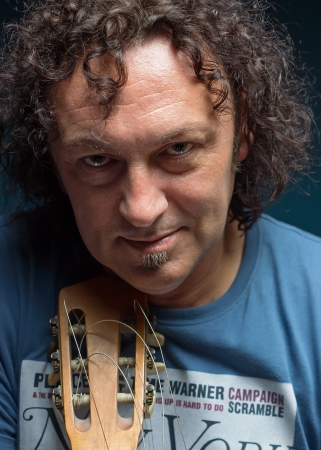 Portrait of a middle-aged man with dark curly hair and guitar
