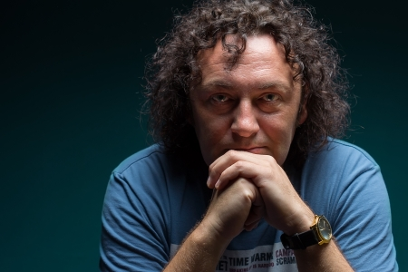 Portrait of a middle-aged man with dark curly hair