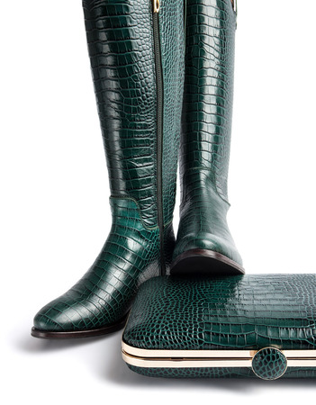 A pair of female green leather boots, and a handbag, isolated on white background
