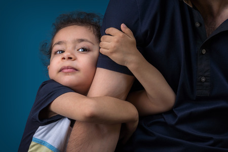 A little boy hugs his father Stock Photo
