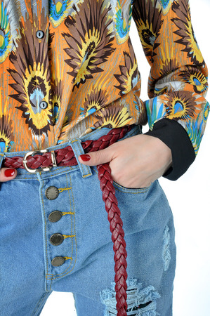 Details of clothes young woman. Jeans, shirt, belt.
