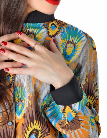 Fragment of female attire. Variegated blouse and manicured hands of the girl.
