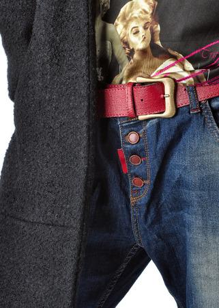 Details of womens clothing. Jeans, belt, shirt, coat.