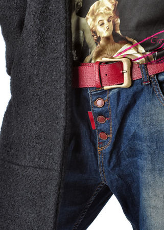 Details of womens clothing. Jeans, belt, shirt, coat.