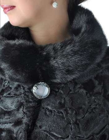 Fragment of female fur coats black. Astrakhan fur coat, mink collar. Stock Photo