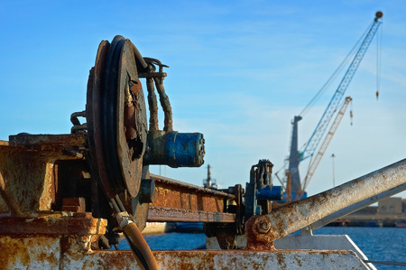 Obsolete equipment on a background of modern cranes in the seaport