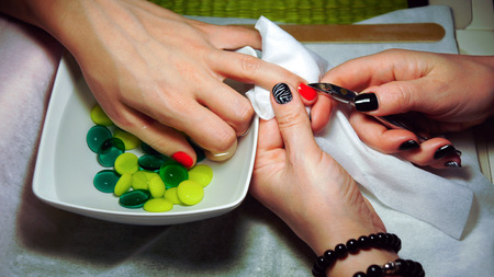 Manicurist makes manicure on female hand