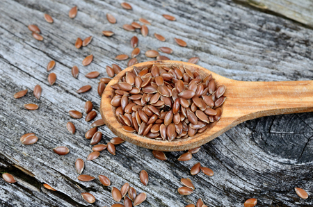 flax seed in spoon on wooden table Stock Photo
