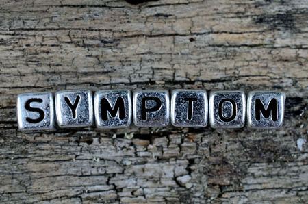 symptom: silver cube word symptom on wooden table