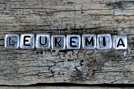 leucemia: silver cube letter word leukemia on cracked wooden table Foto de archivo