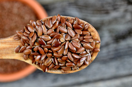 flax seed in wooden spoon on table