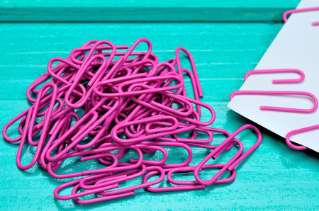 paperclips: pink paperclips on green wooden table