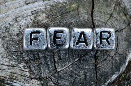 fear: cube word fear on wooden table