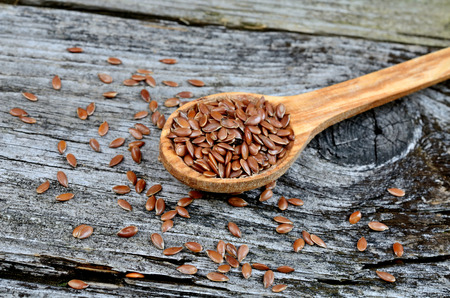 flax seed in spoon on wooden table Imagens