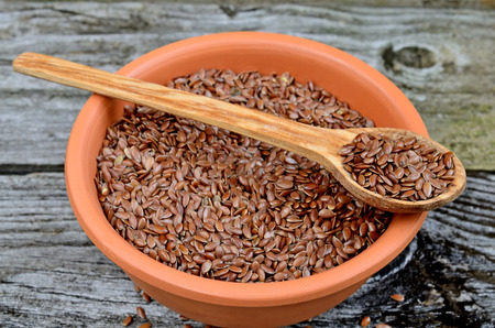 linseed: flax seed in bowl on wooden table Stock Photo