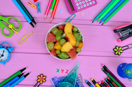 fruit salad and supplies for school on pink wooden table