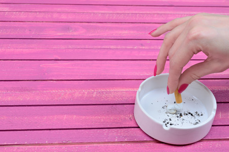 crush: hand of woman crush a cigarette in ashtray on pink wooden table Stock Photo