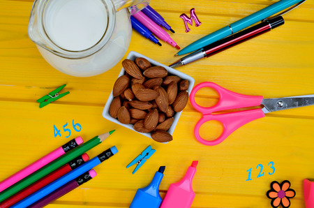 supplies for school with almond and milk on yellow wooden table Stock Photo