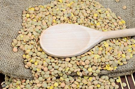 green lentil: wooden spoon on green lentil in sack