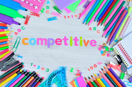 word competitive color letter and stuff for school on gray wooden table Stock Photo