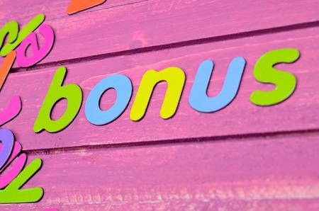 word color letter bonus on pink wooden table