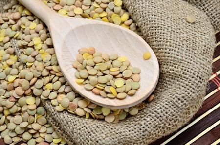 green lentil: pile of green lentil on wooden spoon
