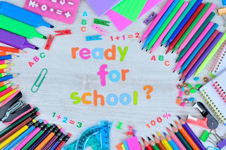 engrapadora: palabra listos para la escuela y otras cosas para la escuela en la mesa de madera de color gris