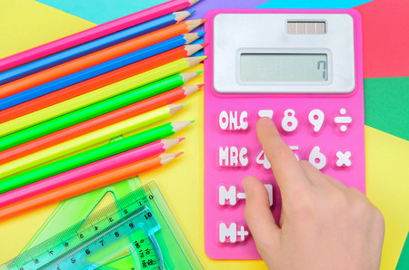 calculate: hand of child calculate on pink calculator Stock Photo