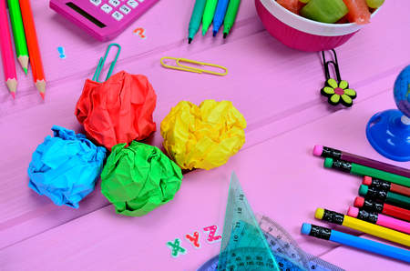 crumpled sheet with supplies for school on pink wooden table