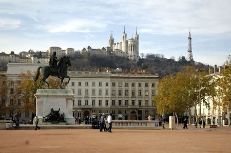 lyon: The Bellecour square in Lyon. Statue of Louis and Basilique Fourviere on a background. France.